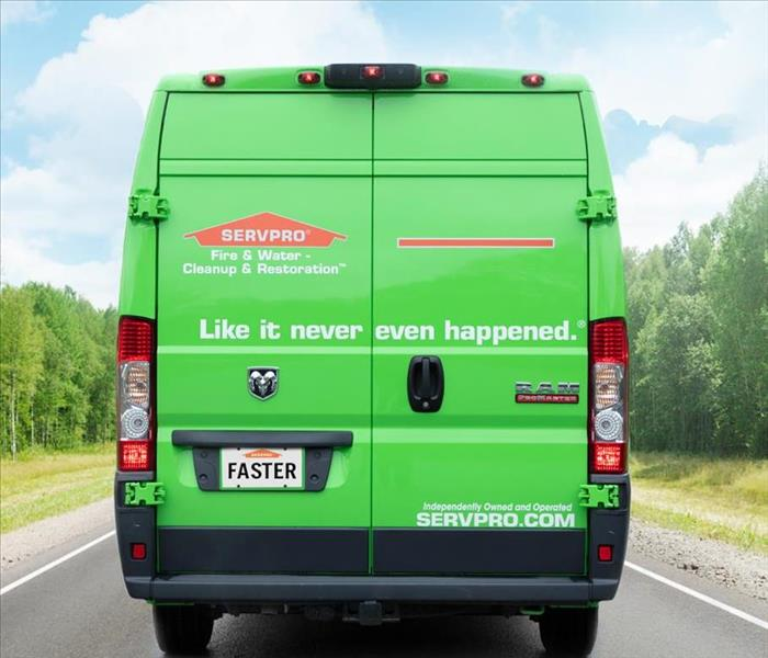 Green SERVPRO van driving down road.