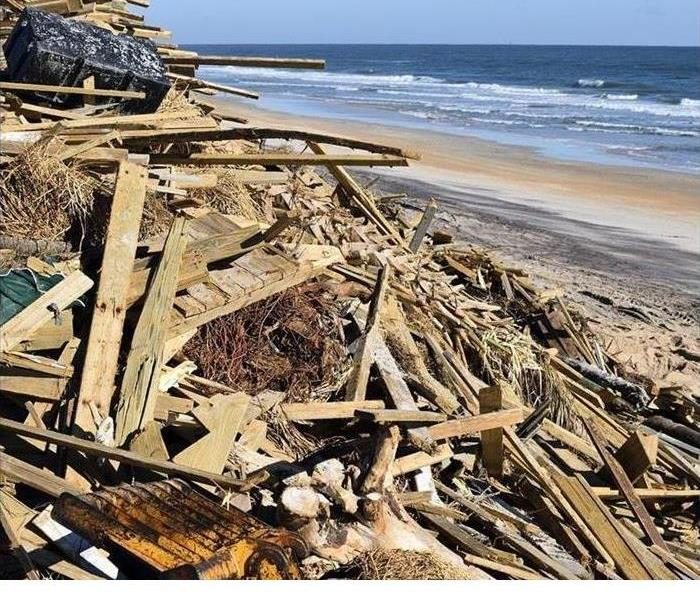 Storm damaged boards are shown on a beach
