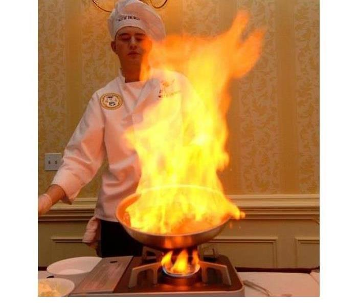 A chef is shown behind a large flame coming from a pan