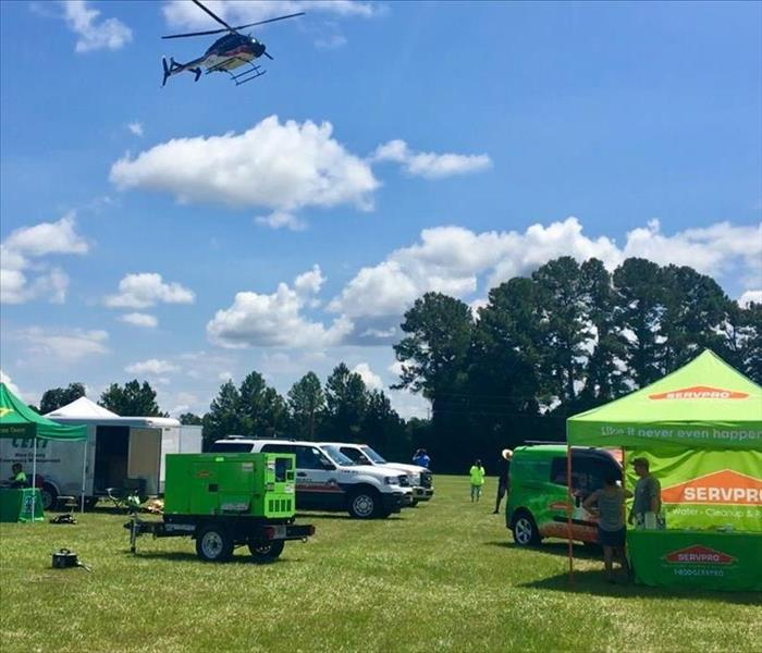 AirEvac Helicopter flys over SERVPRO tent and generator at the event.